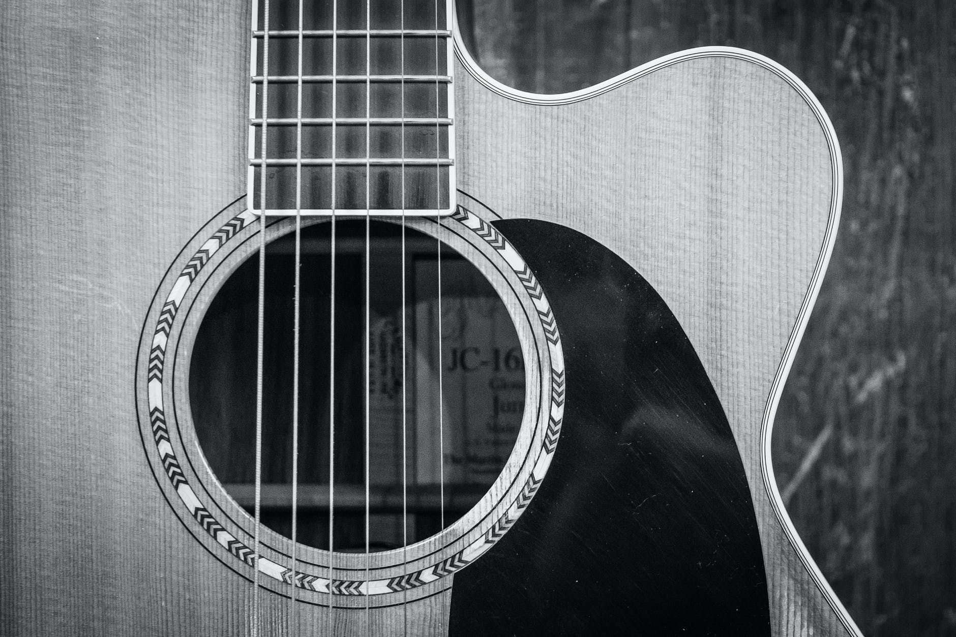 grayscale photo of cutaway acoustic guitar